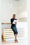 Mujer de negocios elegante sonriente que lleva el vestido negro y los zapatos beige en la oficina ligera que mira su orden del dí Fotos de archivo