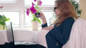 Mujer de negocios embarazada feliz que mira las fotos del ultrasonido almacen de video
