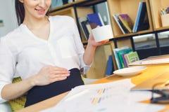 Mujer de negocios embarazada que trabaja en el café caliente de consumición que se sienta de la maternidad de la oficina Fotos de archivo libres de regalías