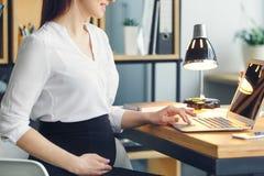 Mujer de negocios embarazada que trabaja en el primer del ordenador portátil de la ojeada de la maternidad de la oficina que se s Fotos de archivo