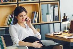 Mujer de negocios embarazada que trabaja en hablar que se sienta de la maternidad de la oficina por el teléfono Fotografía de archivo