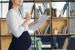 Mujer de negocios embarazada que trabaja en la maternidad de la oficina que se coloca que toma notas foto de archivo
