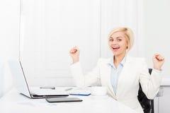 Mujer de negocios emocionada en el escritorio de oficina moderno Foto de archivo