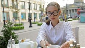Mujer de negocios en café con la tableta Ella bebe noticias del café y de la lectura metrajes