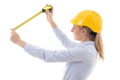 Mujer de negocios en casco del constructor con la cinta de la medida aislada en w fotos de archivo