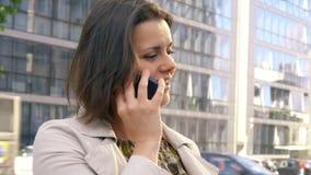 Mujer de negocios en ciudad en el teléfono delante de la oficina almacen de metraje de vídeo