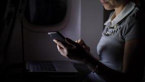 Mujer de negocios en el avión de pasajeros que manda un SMS en smartphone en la noche almacen de metraje de vídeo