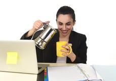 Mujer de negocios en el café de consumición del escritorio del ordenador portátil emocionado y ansioso en el apego del cafeína foto de archivo
