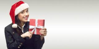 Mujer de negocios en el sombrero de santa que sostiene el regalo Imagen de archivo libre de regalías