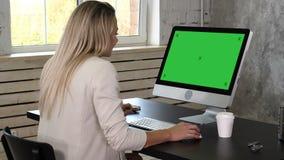 Mujer de negocios en el vestido que se sienta en lugar de trabajo cerca de la ventana y que usa el ordenador en oficina Exhibició almacen de video