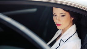 Mujer de negocios en la ventana de su coche oficial Mujer joven hermosa que se sienta en el coche Retrato de una mujer de negocio metrajes
