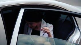 Mujer de negocios en la ventana de su coche oficial Mujer joven hermosa que se sienta en el coche Retrato de una mujer de negocio almacen de video