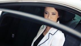 Mujer de negocios en la ventana de su coche oficial Mujer joven hermosa que se sienta en el coche Retrato de una mujer de negocio almacen de metraje de vídeo