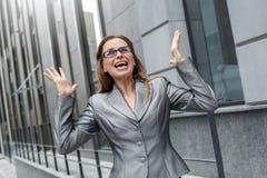 Mujer de negocios en las lentes que se colocan en las manos de la calle de la ciudad para arriba sorprendida con idea imagenes de archivo