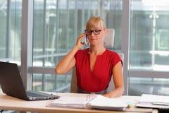 Mujer de negocios en lentes en el teléfono en su oficina Foto de archivo libre de regalías