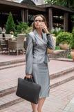 Mujer de negocios en lentes que camina en la calle de la ciudad con el ordenador portátil que habla en el smartphone pensativo foto de archivo