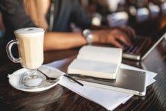 Mujer de negocios en los vidrios interiores con el café y el ordenador portátil que toman notas en restaurante Fotos de archivo libres de regalías