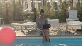 Mujer de negocios en los vidrios que se sientan al lado de la piscina almacen de video