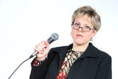 Mujer de negocios en negro con el micrófono Imágenes de archivo libres de regalías