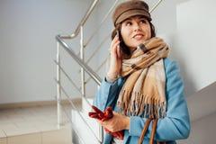 Mujer de negocios en soportes de la capa en las escaleras en la alameda con smartphone Compras Moda fotos de archivo libres de regalías