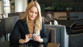 Mujer de negocios en traje con el teléfono que se sienta en una tabla en un café almacen de video