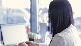 Mujer de negocios en un café con un ordenador portátil metrajes