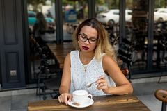 Mujer de negocios en un café que tiene una taza de cappucino imágenes de archivo libres de regalías