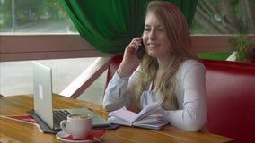 Mujer de negocios en un café que trabaja y que habla en el teléfono elegante almacen de metraje de vídeo