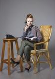 Mujer de negocios en un traje que se sienta en una silla con el talki del teléfono Fotos de archivo libres de regalías