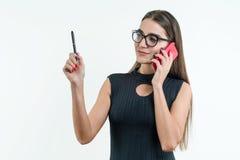 Mujer de negocios en vestido y vidrios negros, hablando en el teléfono, sosteniendo una pluma Estudio blanco del fondo fotografía de archivo