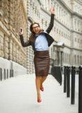 Mujer de negocios encantada que salta para la alegría mientras que habla en el SM Foto de archivo libre de regalías