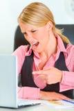 Mujer de negocios enojada en el escritorio que grita en la computadora portátil Imagen de archivo libre de regalías