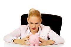 Mujer de negocios enojada que busca su piggybank y que se sienta detrás del escritorio Imagen de archivo