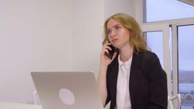 Mujer de negocios enojada que regaña mientras que conversación móvil en oficina de negocios metrajes