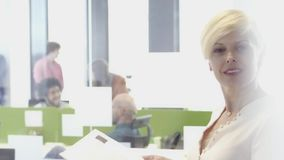 Mujer de negocios envejecida centro sonriente en oficina almacen de metraje de vídeo