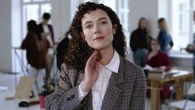 Mujer de negocios europea seria joven en el traje formal que toca su pelo rizado oscuro que presenta en el fondo moderno de la of almacen de metraje de vídeo