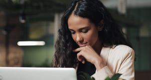 Mujer de negocios experimentada que trabaja con el ordenador portátil que hace la investigación para el inicio de planificación e metrajes