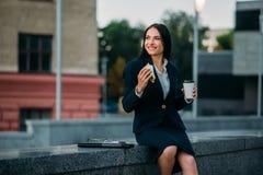 Mujer de negocios feliz con el bocadillo y el café fotos de archivo