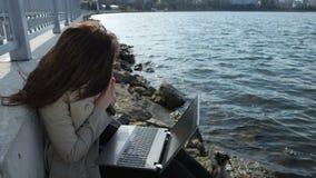 Mujer de negocios feliz con un ordenador portátil que se sienta encendido metrajes