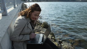 Mujer de negocios feliz con un ordenador portátil que se sienta encendido almacen de metraje de vídeo