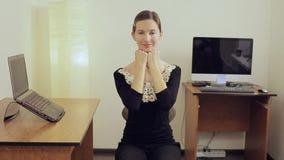 Mujer de negocios feliz en la oficina que estira su cuello mientras que se sienta cerca del escritorio metrajes