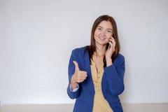 Mujer de negocios feliz en ropa casual que invita al teléfono en oficina imagen de archivo