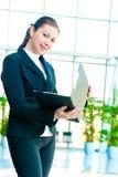 Mujer de negocios feliz joven con una carpeta abierta a disposición Imagenes de archivo