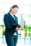 Mujer de negocios feliz joven con una carpeta abierta a disposición Imagen de archivo libre de regalías