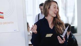 Mujer de negocios feliz joven del CEO del caucásico con la cartera que explica el diagrama financiero a los colegas en la reunión almacen de video
