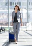 Mujer de negocios feliz que camina con la maleta en el aeropuerto Imagen de archivo