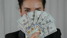 Mujer de negocios feliz que exhibe una extensión del efectivo Foto de archivo libre de regalías