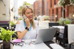 Mujer de negocios feliz que habla en el teléfono y que usa el ordenador Imagen de archivo libre de regalías