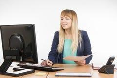 Mujer de negocios feliz que mira el ordenador que los datos deseados en el documento enumeran Foto de archivo