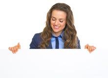 Mujer de negocios feliz que mira en la cartelera en blanco Foto de archivo